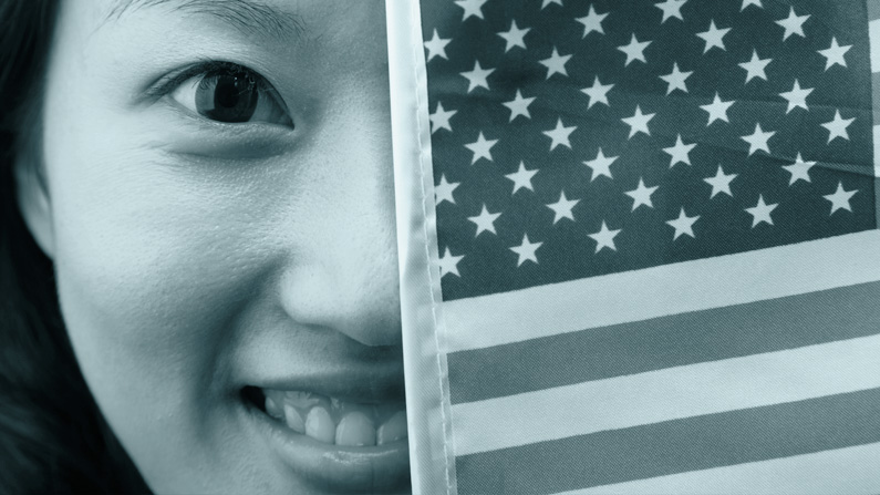 Young woman smiling shows half her face with the other half covered by a USA flag for elections